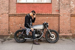Brutal man sit on cafe racer custom motorbike. Handsome rider biker man in black leather jacket and protection glasses sit on classic style cafe racer stock photography