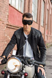 Brutal man sit on cafe racer custom motorbike. Handsome rider biker man in black leather jacket and sunglasses googles sit on classic style cafe racer stock photos