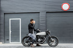 Brutal man sit on cafe racer custom motorbike. Stock Photography