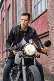 Brutal man sit on cafe racer custom motorbike. Handsome rider biker guy in black leather jacket, jeans, boots and gloves sit on classic style cafe racer stock image