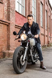 Brutal man sit on cafe racer custom motorbike. Handsome rider biker guy in leather jacket sit on classic style cafe racer motorcycle and ready for long ride stock photo
