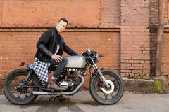 Brutal man sit on cafe racer custom motorbike. Handsome rider biker guy in leather jacket sit on classic style cafe racer motorcycle. Side view. Horizontal royalty free stock photo