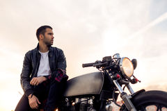 Brutal man sit on cafe racer custom motorbike. Handsome rider boy with beard and mustache in black leather biker jacket sit on classic style cafe racer stock photography