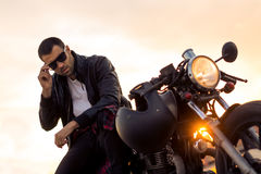 Brutal man sit on cafe racer custom motorbike. Handsome rider guy with beard and mustache in black biker jacket put on sunglasses sit on classic style cafe stock images