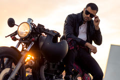 Brutal man sit on cafe racer custom motorbike. Handsome rider guy with beard and mustache in black biker jacket take off sunglasses on classic style cafe racer Royalty Free Stock Photos