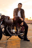 Brutal man sit on cafe racer custom motorbike. Handsome rider guy with beard and mustache in black leather biker jacket, boot and jeans sit on classic style stock image