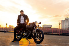 Brutal man sit on cafe racer custom motorbike. Handsome rider guy with beard and mustache in black leather biker jacket sit on classic style cafe racer stock photo