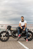 Brutal man sit on cafe racer custom motorbike. Handsome rider guy with a beard and mustache sit on classic style biker cafe racer motorcycle and ready for long royalty free stock image
