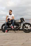 Brutal man sit on cafe racer custom motorbike. Handsome rider guy with a beard and mustache sit on classic style biker cafe racer motorcycle and and wait his stock image