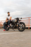 Brutal man sit on cafe racer custom motorbike. Handsome rider guy with beard and mustache in red sneakers and black moto glasses sit on classic style biker cafe stock images