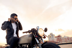 Brutal man sit on cafe racer custom motorbike. Stock Images