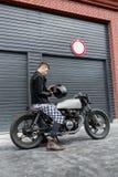 Brutal man sit on cafe racer custom motorbike. stock photography