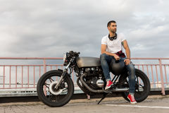 Brutal man sit on cafe racer custom motorbike. Rider man with beard and mustache in red sneakers and white t-shirt sit on classic style biker cafe racer royalty free stock image