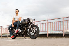 Brutal man sit on cafe racer custom motorbike. Rider guy with beard and mustache in red sneakers sit on classic style biker cafe racer motorcycle with black royalty free stock image