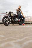 Brutal man sit on cafe racer custom motorbike. Rider guy with beard and mustache in red sneakers sit on classic style biker cafe racer motorcycle with black stock photo
