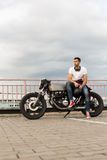 Brutal man sit on cafe racer custom motorbike. Rider guy with beard and mustache in red sneakers and white t-shirt sit on classic style biker cafe racer stock photos