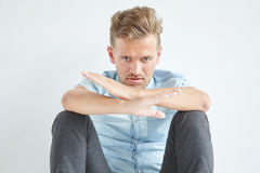Brutal man sitting on the floor. Under the gaze of the forehead, arms crossed, in a shirt with short sleeves Stock Photo
