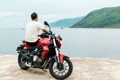 Man sitting on his motorcycle and looking at the sea. Brutal man sitting on his motorcycle and looking at the sea Royalty Free Stock Photography