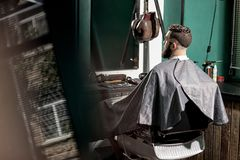 Brutal man with stylish hairstyle and beard sits at a barber shop in front the mirror. Brutal men with stylish hairstyle and beard sits at a barber shop in front stock photography