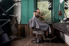 Brutal man with tha beard sits in the chair in front the mirror at a barber shop . Barber shaves mans hairs stock images