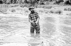 Brutal man wear rubber boots stand in river water. Satisfied fisher. Fisher masculine hobby. Fisher fishing equipment