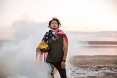 Brutal man wearing usa flag cape posing in white smoke Royalty Free Stock Images