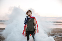 Brutal man wearing usa flag cape posing in white smoke Royalty Free Stock Photography