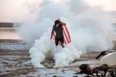 Brutal man wearing usa flag cape posing in white smoke Royalty Free Stock Photo