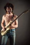 Brutal manmusiker som spelar gitarren Royaltyfri Bild