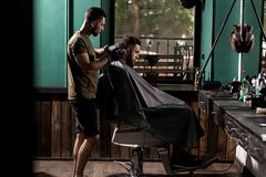 Brutal man with beard sits in a chire at a barber shop. Handsome barber shaves hairs at the side. stock images