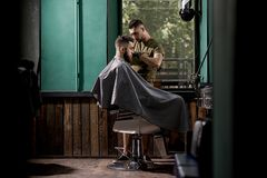 Brutal man with beard sits in a chire at a barber shop. Handsome barber shaves hairs at the side. stock photo