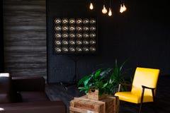 Brutal modern inre i en mörk färg med en lädersoffa Vindstilvardagsrum royaltyfri foto