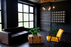 Brutal modern interior in a dark color with a leather sofa and large window. Loft style living room royalty free stock photography