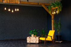 Brutal modern interior in a dark color with a yellow leather chair. Loft style living room stock images
