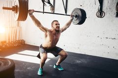 Brutal muscular man with beard train with barbell raised over head in gym royalty free stock photos