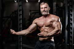 Brutal muscular man with beard unshaven fitness model healthcare. Brutal muscular man with beard train in the gym unshaven fitness model healthcare lifestyle Stock Photo