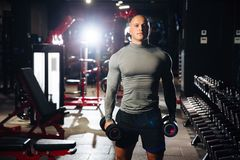 Brutal muscular man doing sport exercises with dumbbells in the gym. A strong guy is engaged in fitness. Concept sport. Health stock photography