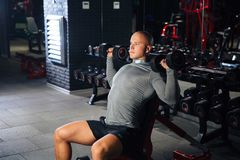 Brutal muscular man doing sport exercises with dumbbells in the gym. A strong guy is engaged in fitness. Concept sport. Health stock photos