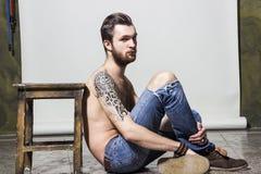 Brutal muskulös sexig inked hårig orakad ung man med tatueringen på hans skuldra och skägg Royaltyfria Bilder