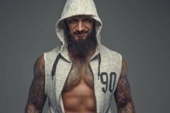 Brutal muskulös tatuerad bög i grå sportdräkt arkivfoton