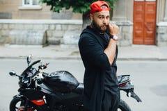 Brutal och muskulös skäggcyklist på motorcykeln Royaltyfria Foton