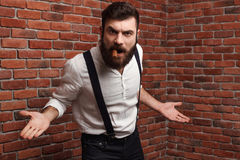 Brutal rage young handsome man smoking cigar over brick background. Royalty Free Stock Image