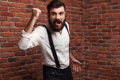 Brutal rage young handsome man smoking cigar over brick background. Stock Photo