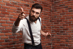 Brutal rage young handsome man smoking cigar over brick background. Royalty Free Stock Photos