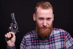 Attractive man with revolver and beard royalty free stock photos
