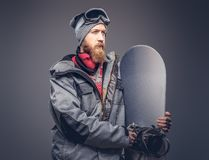 Brutal redhead snowboarder with a full beard in a winter hat and protective glasses dressed in a snowboarding coat stock photo
