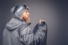 Brutal redhead snowboarder with a full beard in a winter hat and protective glasses dressed in a snowboarding coat stock images