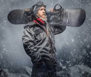 Brutal redhead snowboarder with a full beard in a winter hat and protective glasses dressed in a snowboarding coat. Posing with snowboard against the background stock photos