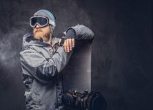 Brutal redhead snowboarder with a full beard in a winter hat and protective glasses dressed in a snowboarding coat. Redhead brutal snowboarder with a full beard stock image