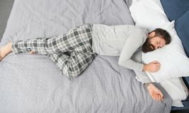 brutal s?mnig man i sovrum mogen man med sk?gget i pajama p? s?ng sovande och vaket energi och tr?tthet _ royaltyfria foton